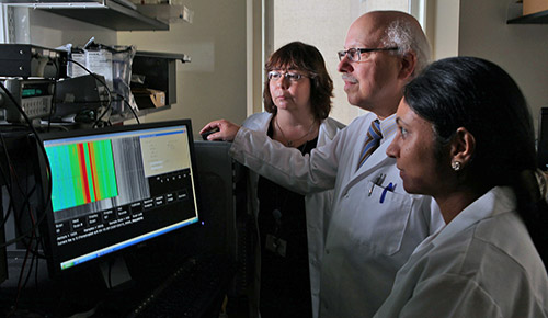 Researchers look at results on a screen